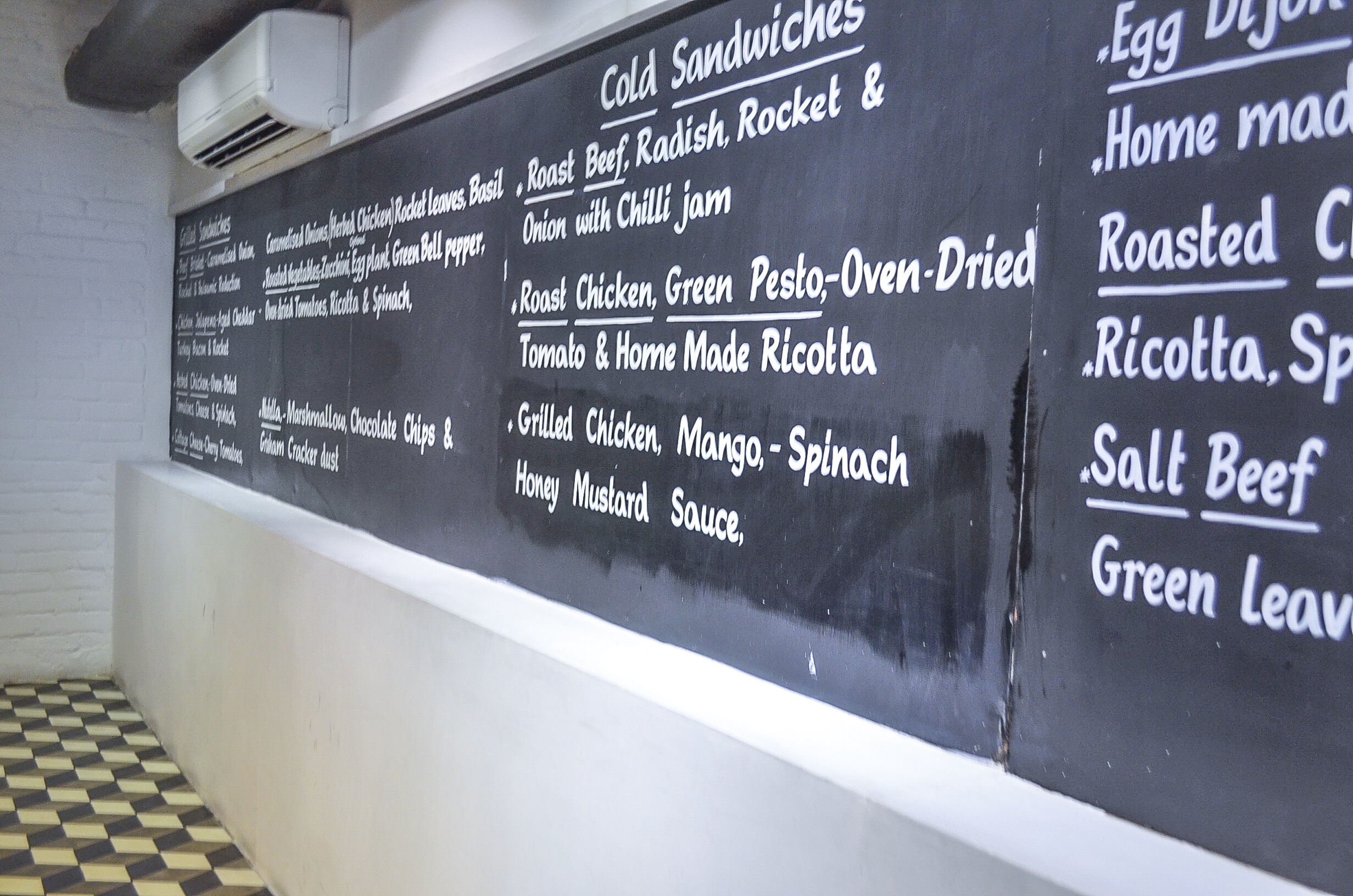 Menu 'chalked' on blackboard opposite the salad counter at Mall One - love the retro looking floor design!
